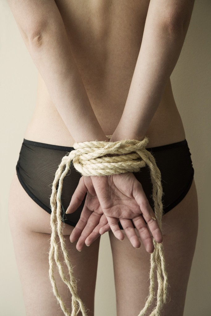 Female hands bound in rope
