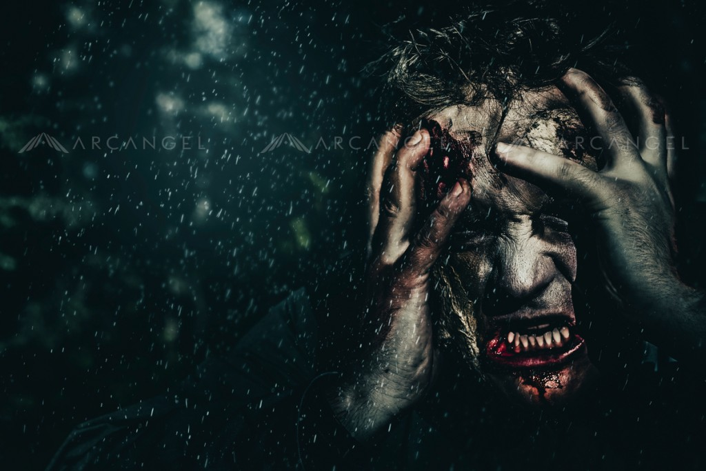Evil zombie man expressing fear when turning into the living dead at dark haunted forest. Gripping terror