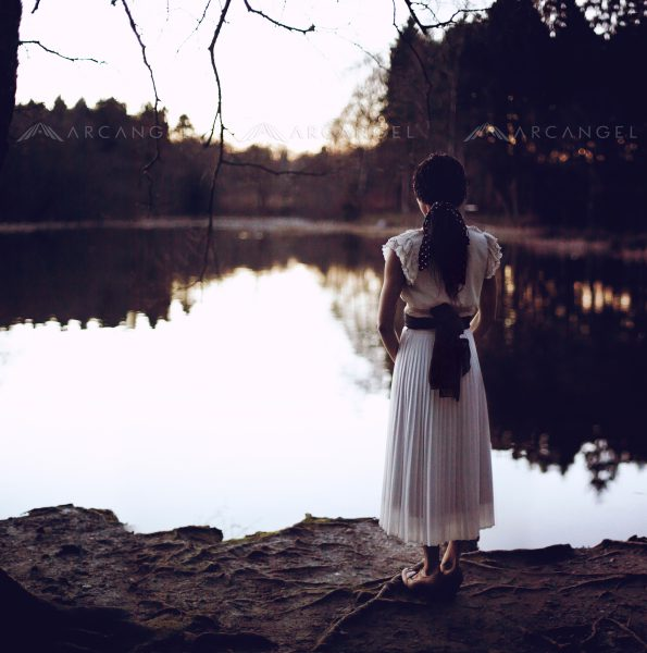 Girl stands overlooking lake at fall of night